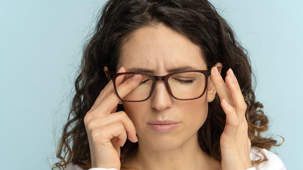Una mujer con lentes se frota los ojos.