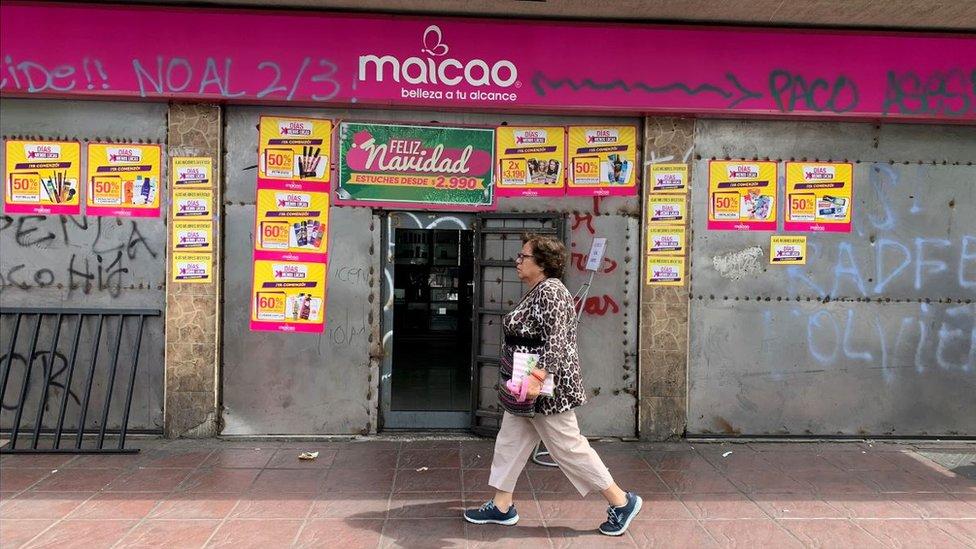 Mujer pasa frente a un comercio en Valparaíso