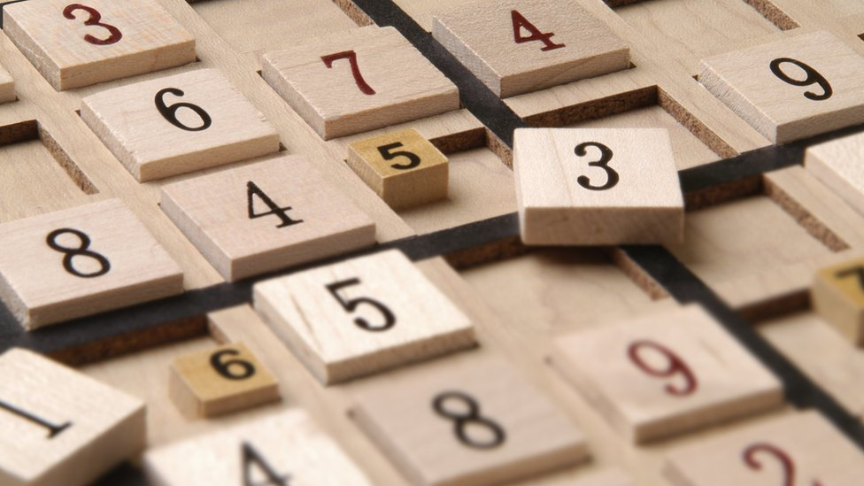 Close up of a wood Sudoku Game Board with puzzle in progress
