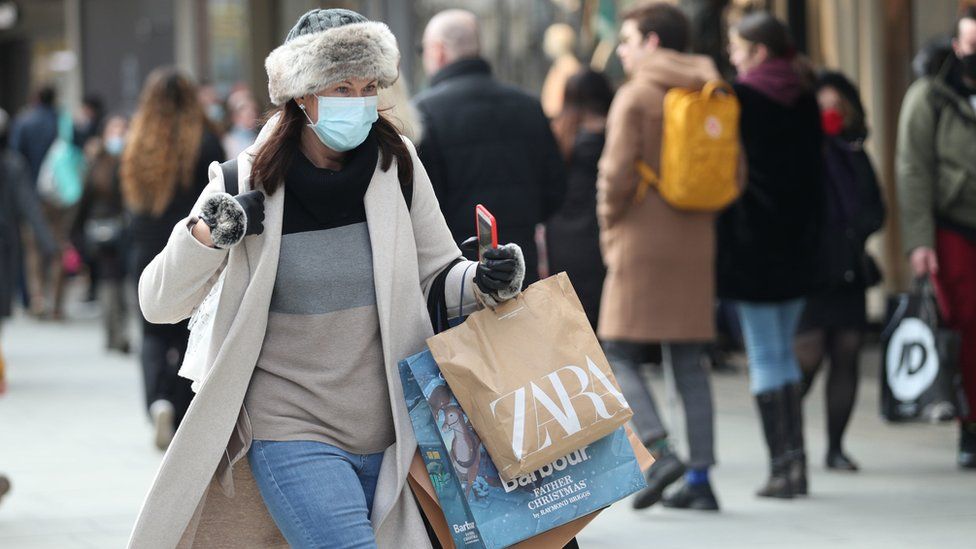 Woman in mask laden with shopping bags on first Saturday after lockdown ended
