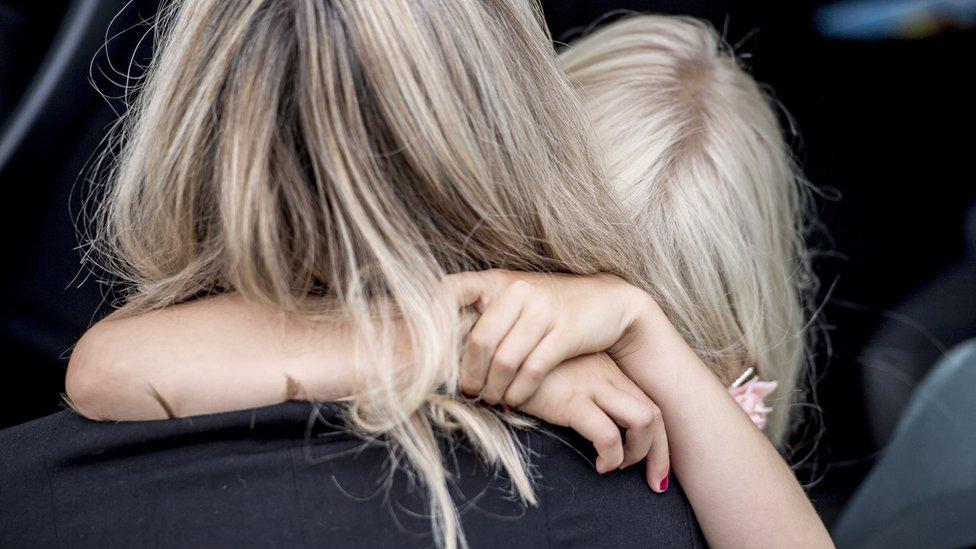 Дівчинка-блондинка обіймає маму