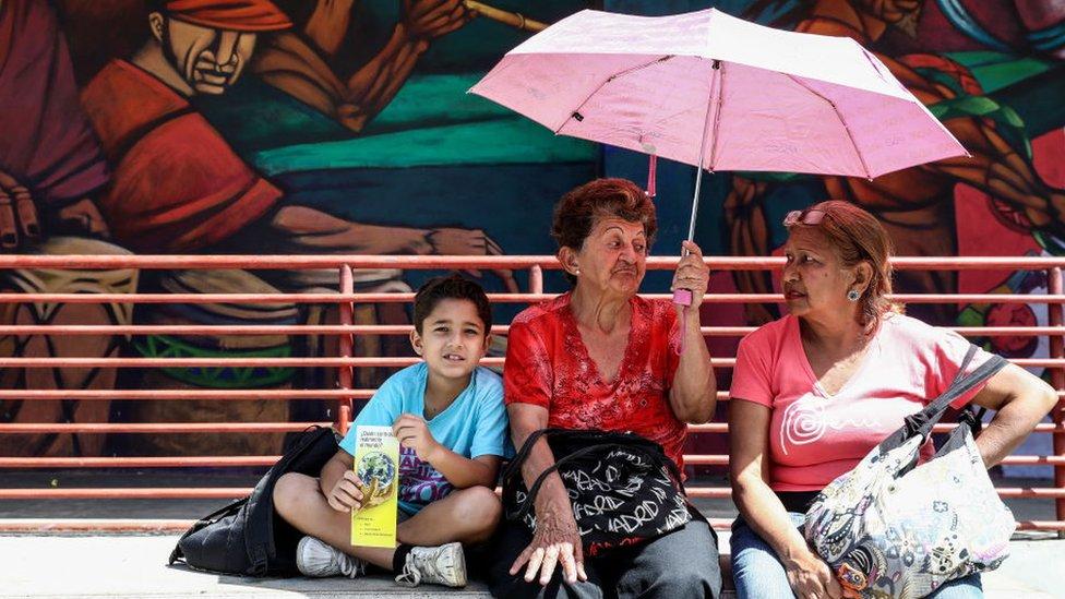 Un niño en una calle de Caracas sentado junto a dos mujeres mayores.