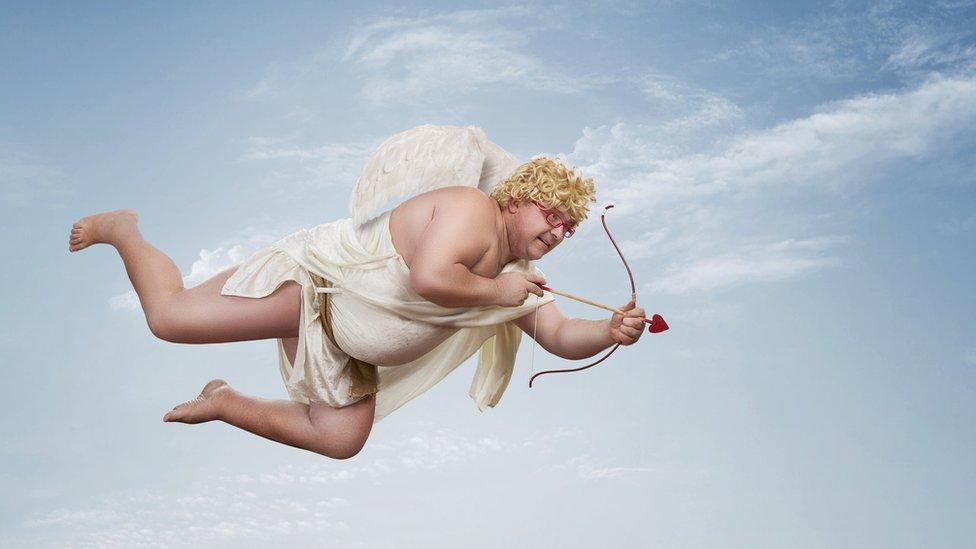 Hombre vestido como Cupido volando