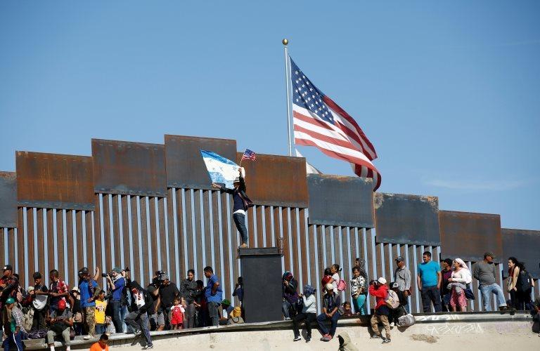 Migrantes junto al muro fronterizo en Tijuana