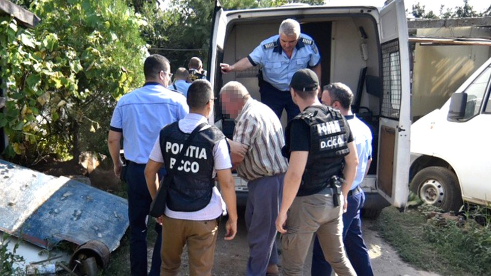 Romanian police officers escort suspect Gheorghe Dinca (C) to his home for a search of the property on 27 July, 2019