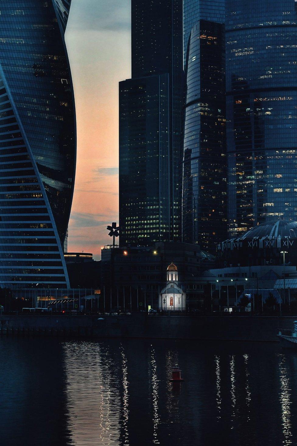 俄國首都莫斯科,林立的摩天大樓中矗立著一座燈光溫暖的教堂。