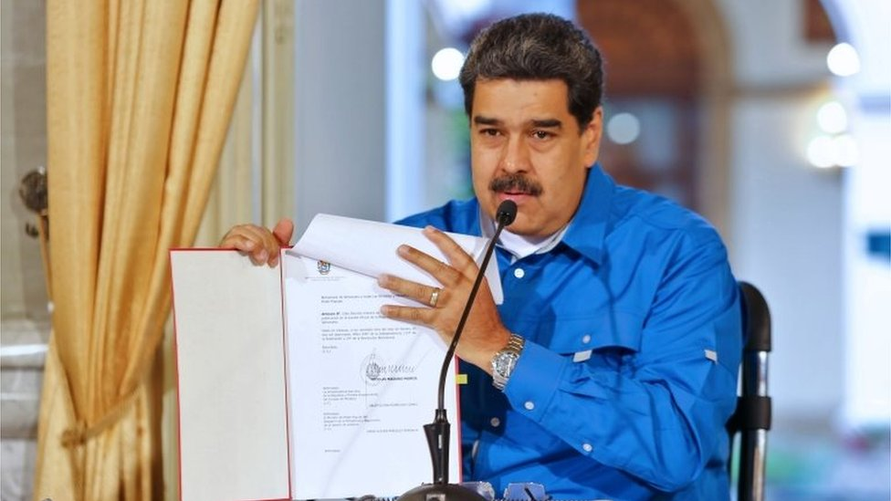 Handout picture released by the Venezuelan Presidency press office of Venezuela's President Nicolas Maduro showing a document as he gives a message in Caracas on February 27, 2019.