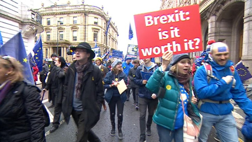 People marching through Leeds with anit-anti placards