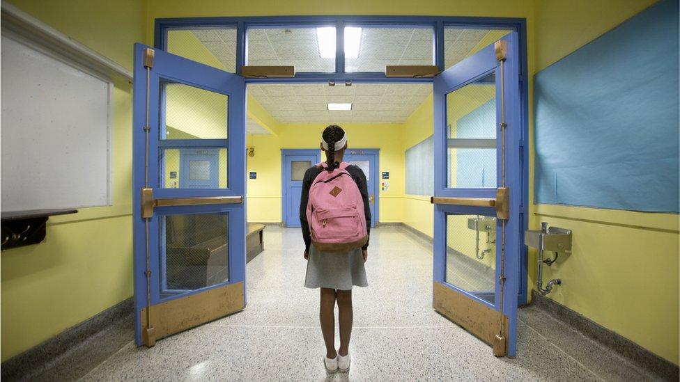 Una estudiante camina por el pasillo de una escuela.