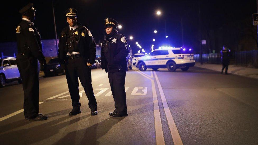 Tres policías en una calle cerrada, de noche