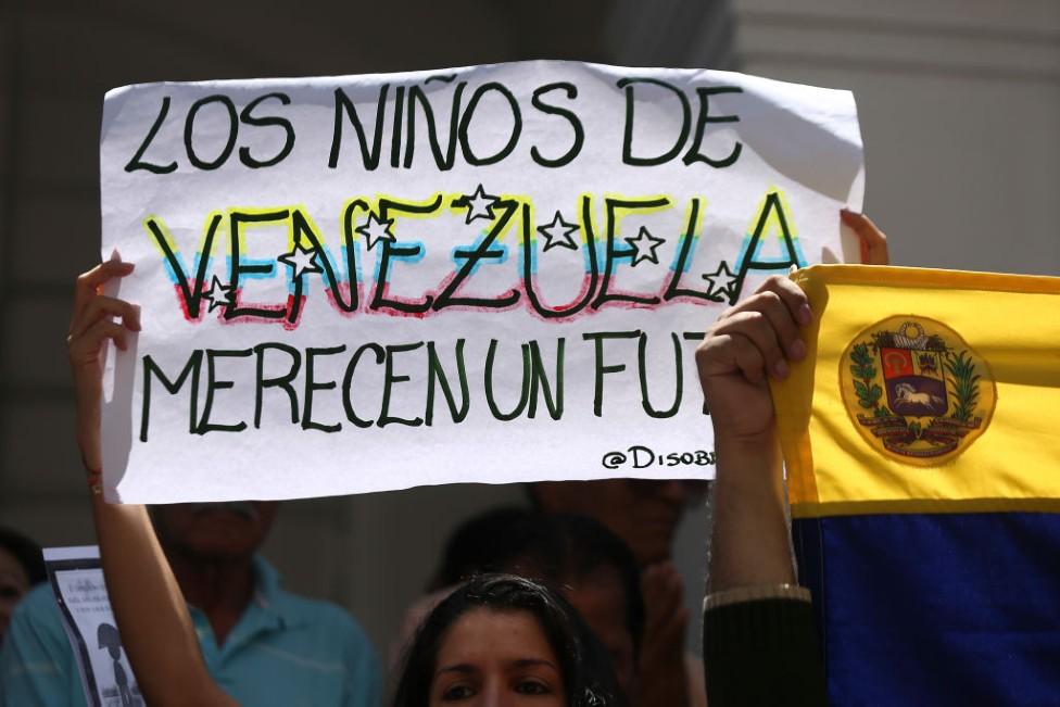 Una manifestante con una pancarta que dice: Los niños de Venezuela merecen un futuro