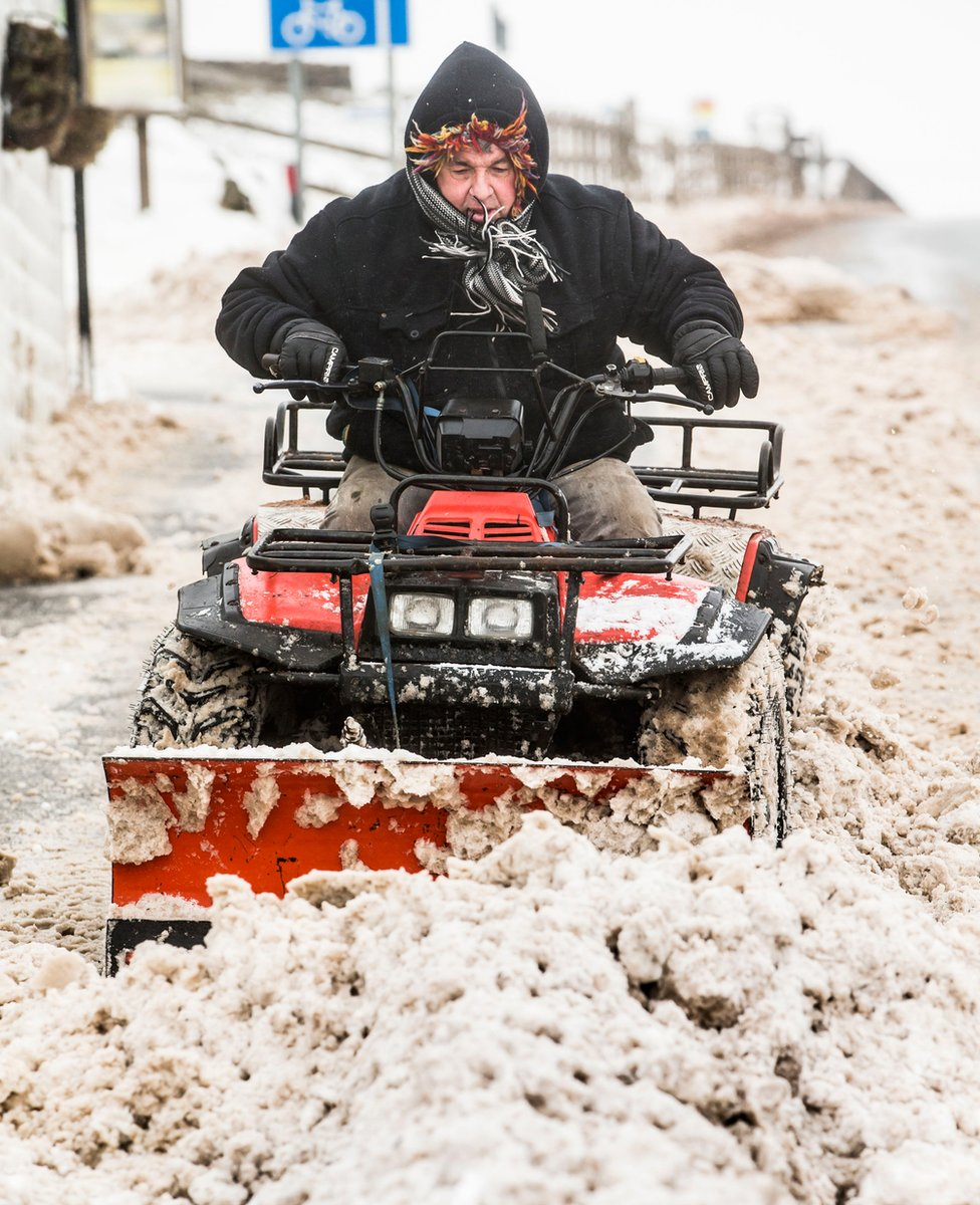 A man clears snow near Blackstone Edge in the Pennines