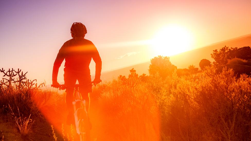 Hombre andando en bicicleta con una puesta de Sol de fondo
