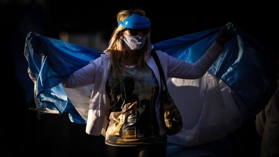 Mulher protesta usando máscara e com uma bandeira da Argentina em volta do corpo