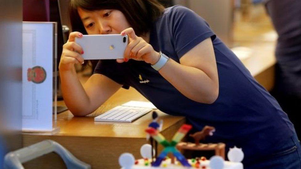 سيدة صينية تستخدم أيفون للتصوير