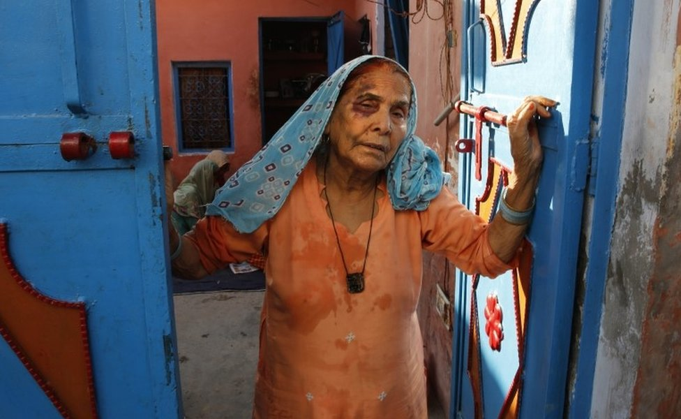 A bruised Asgari Begum, mother of 52-year-old Muslim farmer Mohammad Akhlaq, stands by the entrance of her home in Bisada