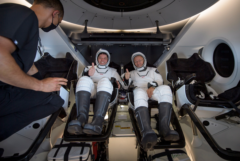 Astronauts Robert Behnken and Douglas Hurley give a thumbs up as they sit inside the SpaceX Crew Dragon Endeavour spacecraft