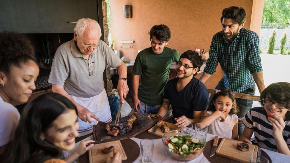 Adultos, adolescentes e crianças se reúnem em volta de uma mesa, onde um homem idoso corta uma carne de churrasco
