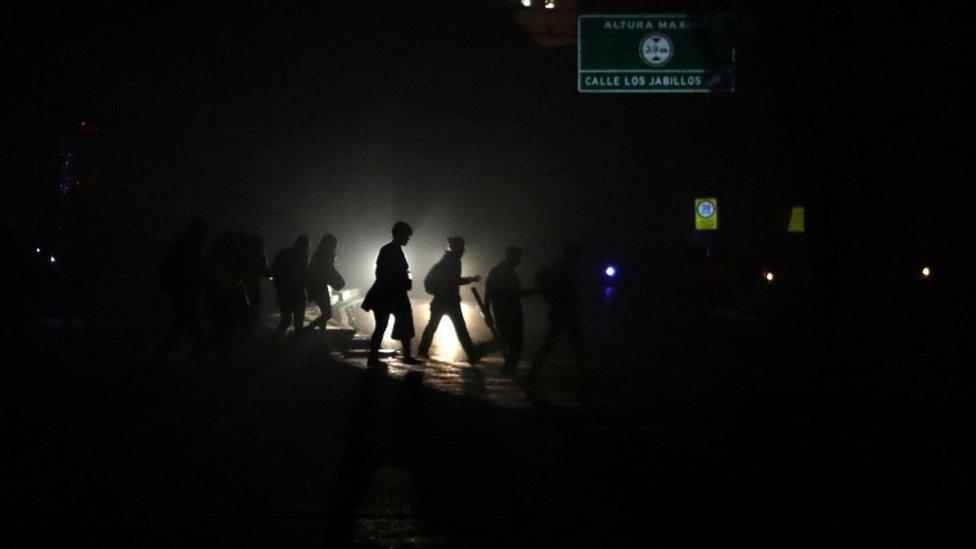Gente caminando a su casa a oscuras.