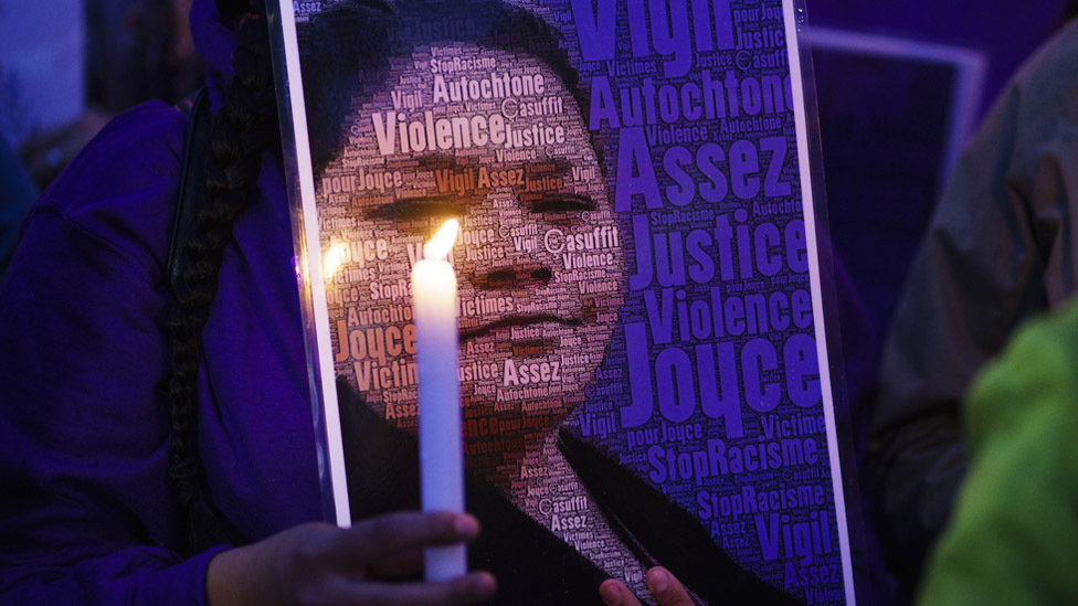 A woman at a vigil holds a candle in front of an image of Joyce Echaquan