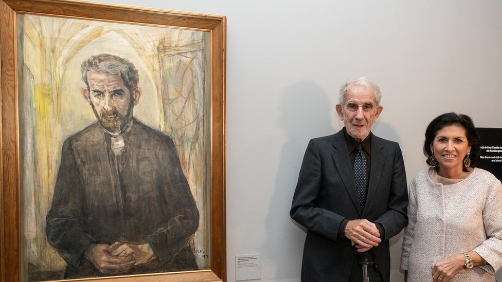 Victor de Waal (second right) stands beside a painting of himself as Dean of Canterbury Cathedral