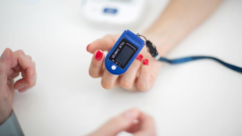 Oxímetro en la mano de una paciente.