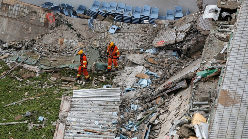 """Two firefighters walk through the debris of the collapsed section of a building at the City University""""s campus in Hong Kong"""