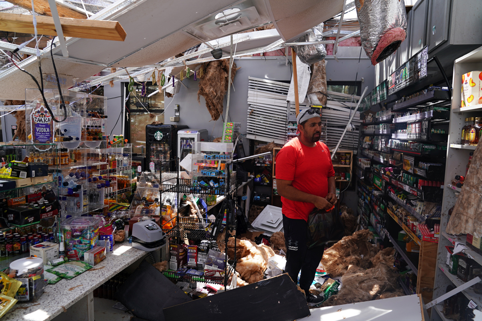 Ahmed Nawaz surveys the damage to his store in Louisiana