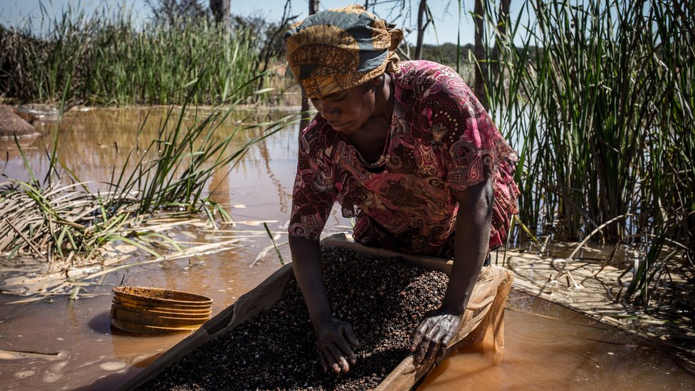 Una mujer separa cobalto del barro y rocas cerca de una mina en la RDC.