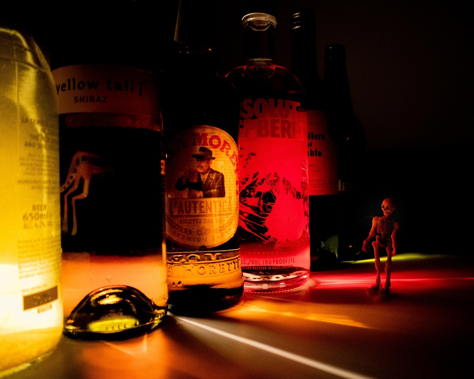A row of bottles of alcohol with a small skeleton toy