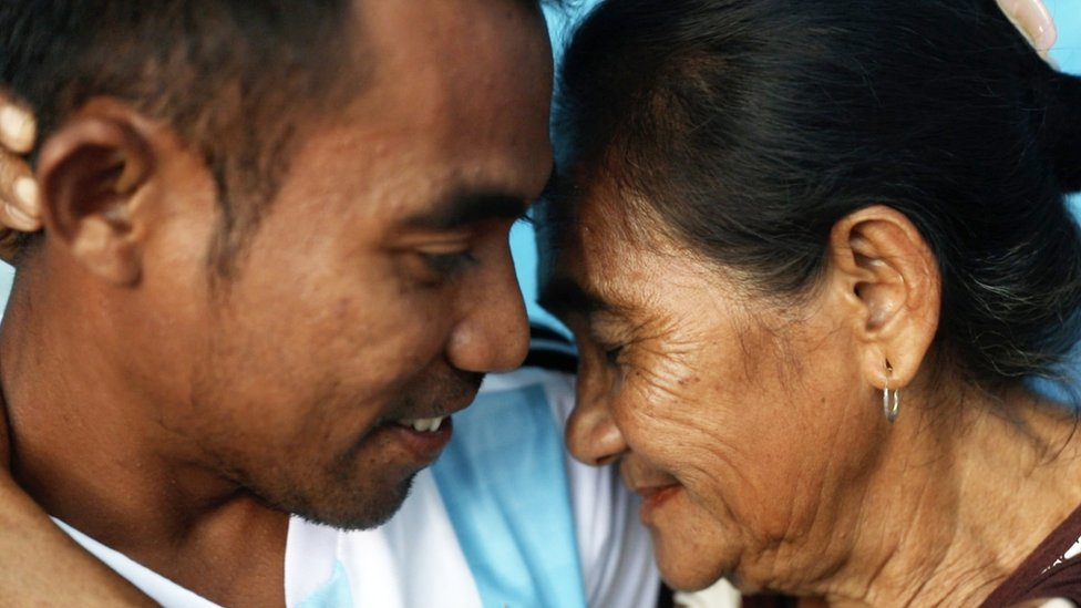 Siti Rudy and Abdul touch their heads together in an embrace at home in Indonesia