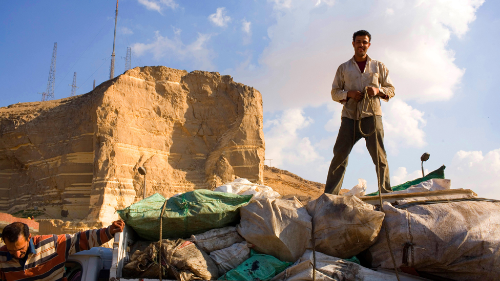 A Zabaleen ties up sacks of garbage on his truck near the Cairo suburb of Moqqatam