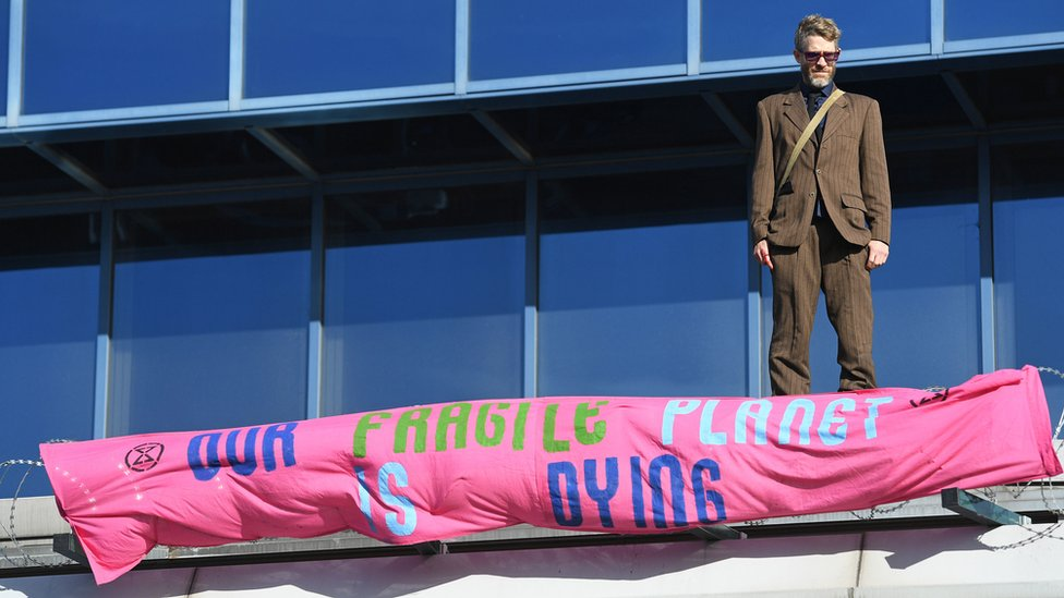A protester stands on the roof of the terminal building at London City Airport