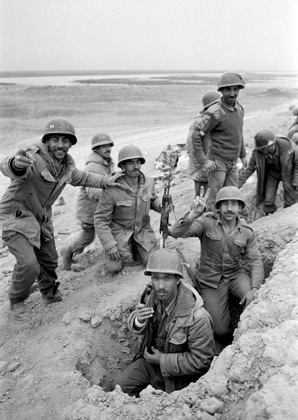 An Iraqi soldier flashes a V-sign as his comrades look on, in a trench dug near Al Boweizah swamps, north of Basra on March 18, 1985