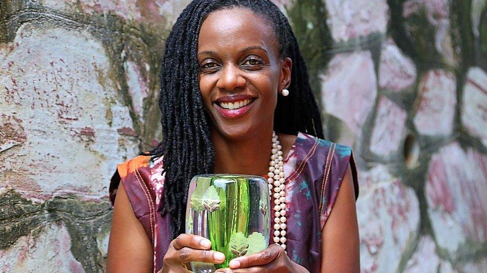 Catherine Nakalembe holding award