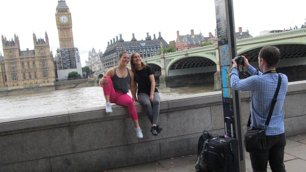 A man taking two women's photograph