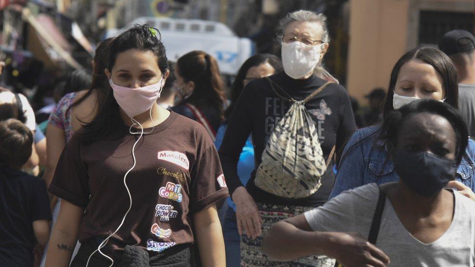 Pessoas na rua com máscara