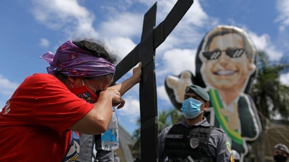متظاهر يحمل صليبا في احتجاج على بولسونارو وتعامله مع الوباء