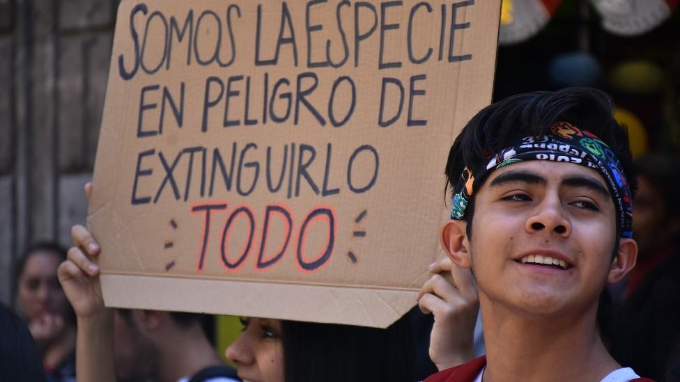 """Jóvenes en México con una pancarta que dice """"somos la especie en peligro de extinguirlo todo""""."""