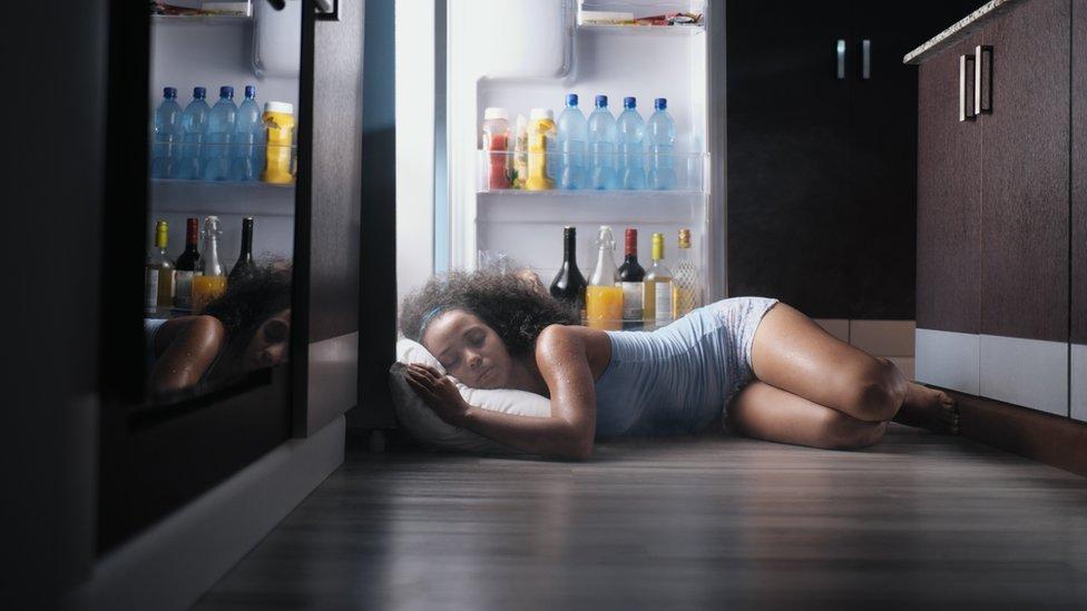 A woman sleeping next to a fridge