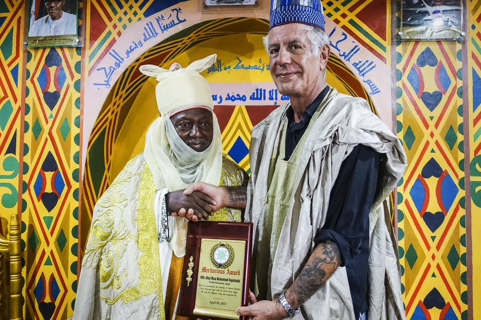 Bourdain accepts an award during a visit to Nigeria.