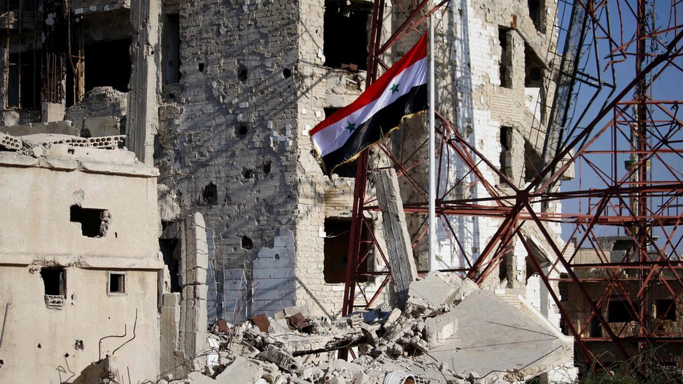 Syrian national flag flies in the previously rebel-held part of Deraa city, Syria (12 July 2018)
