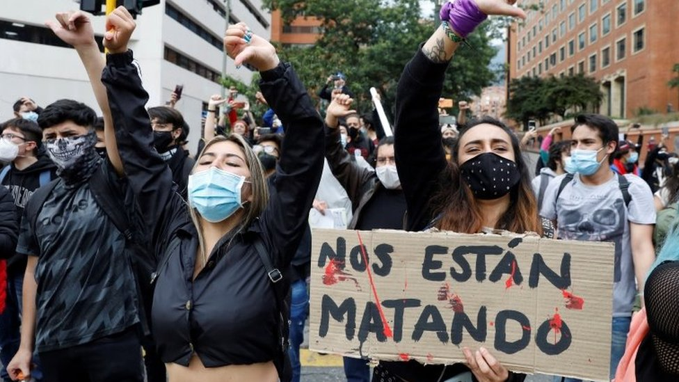 """Manifestantes en Bogotá con un letrero que dice """"Nos están matando""""."""