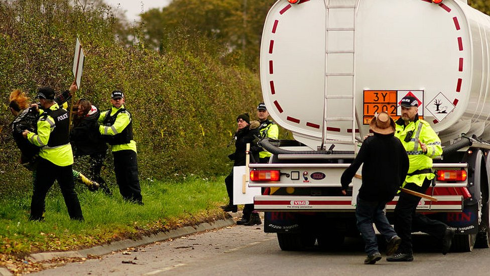Police officers restrain an anti-fracking protester attempting to stop a tanker lorry leaving the Preston New Road