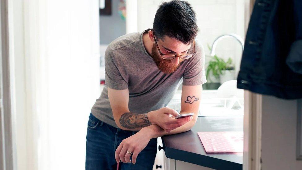 Un hombre mirando su celular