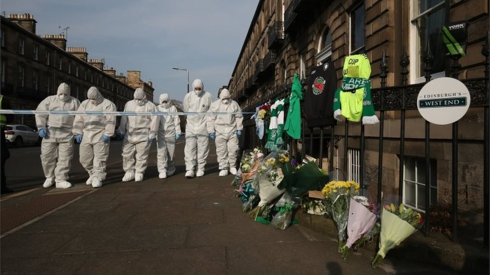 Forensic officers and tributes at the scene