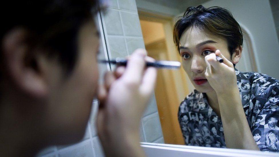 Hombre de rasgos asiáticos maquillándose frente al espejo.