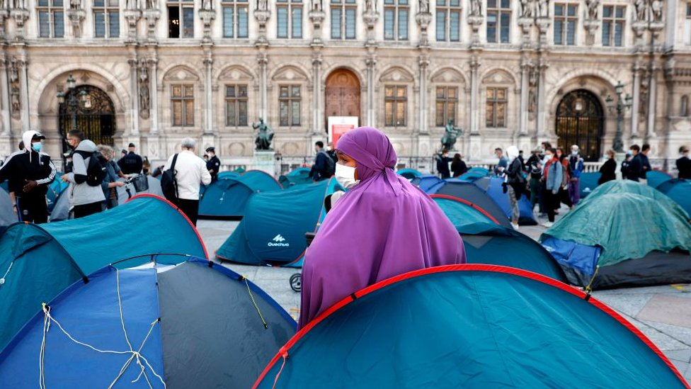 A woman with a mask stands as migrants are evacuated by police in front of the town hall of Paris, on September 1, 2020