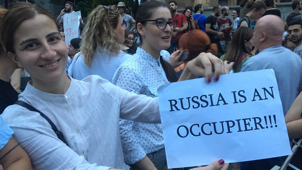 A protester holds up a piece of paper accusing Russia of occupying Georgian lands