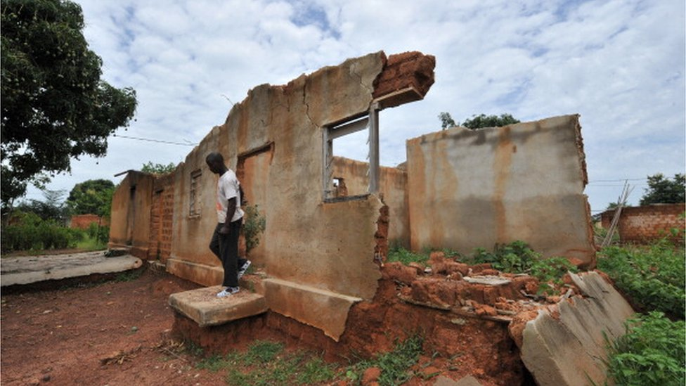 A man walks through a house destroyed during post-electoral violence that occurred in 2011 in the western Ivory coast village of Niambli, near Duekoue on April 21, 2012